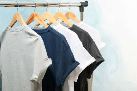Rack with blank t-shirts on blue background, space for text Stockfoto