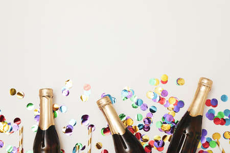 Composition with mini champagne bottles and glitter on white background, copy space