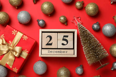 Christmas baubles and wooden calendar on red background, top view 版權商用圖片