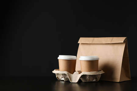 Eco - friendly package and coffee cups on black background, space for text Stock fotó