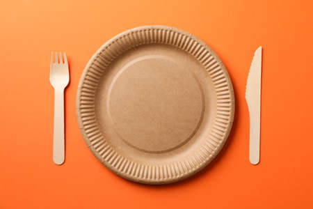 Flat lay with eco - friendly tableware on orange background, space for text