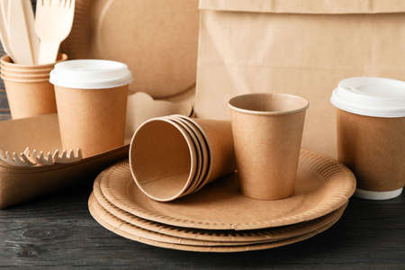 Eco - friendly tableware and paper bag on wooden table, close up 版權商用圖片