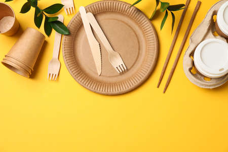 Concept with eco - friendly tableware and plant on yellow background, copy space