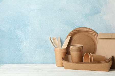 Eco - friendly tableware and paper bag on wooden table, space for text 版權商用圖片