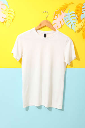 Hanger with blank white t-shirt on two tone background, space for text