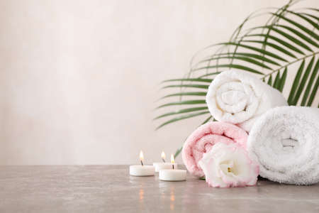 Towels, candles and flower on grey background, space for text
