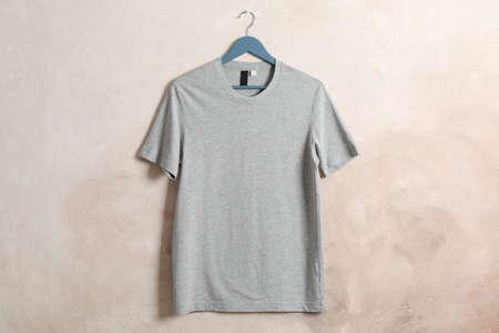 Kleiderbügel mit leerem grauem T-Shirt auf braunem Hintergrund, Platz für Text