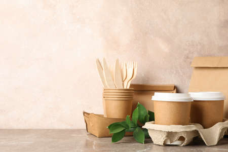 Eco - friendly tableware and paper bag on grey table, space for text Reklamní fotografie