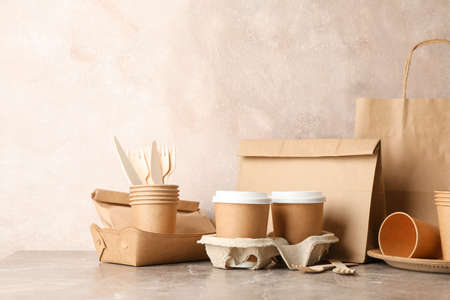Eco - friendly tableware and paper bag on grey table, space for text Stockfoto