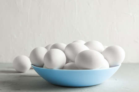 Chicken eggs in plate on gray table against white background, space for text Stock Photo