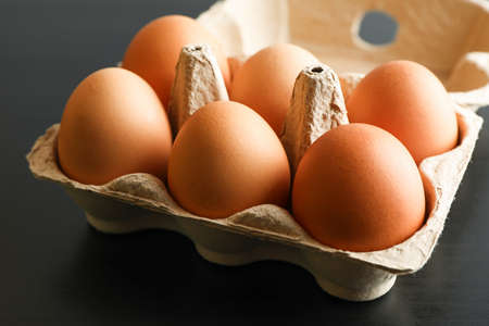 Chicken eggs in carton box on black background, space for text