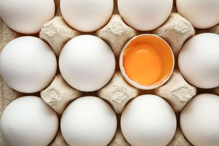 Chicken eggs in carton box as background, space for text