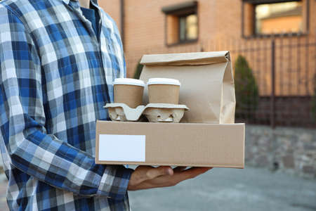 Man holds blank box, coffee cups and paper package outdoor. Delivery