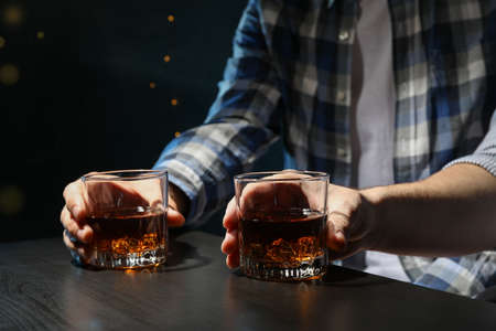 Men drink whiskey at the bar, close up. Blurred lights Stock Photo