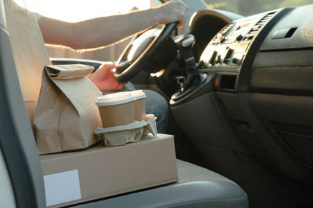 Blank box, coffee cups, paper packages and courier in car. Delivery