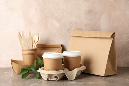 Eco - friendly tableware and paper bag on grey table, space for text