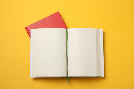 Opened empty book and red book on yellow background, space for text 免版税图像