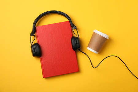 Red book, headphones and coffee cup on yellow background, space for text
