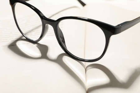 Heart made of shadow and glasses on opened book, close up 免版税图像