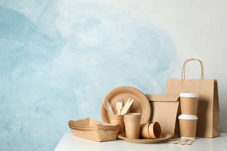 Eco - friendly tableware and paper bag on white table, space for text Stock Photo