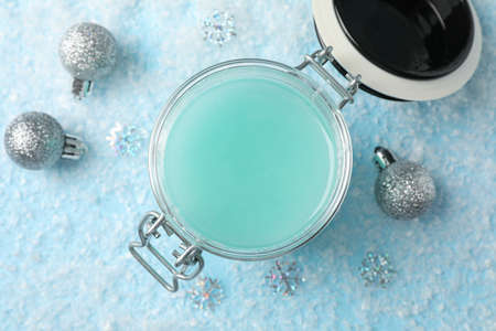 Jar of winter cream for skin on snowy blue background, space for text. Top view