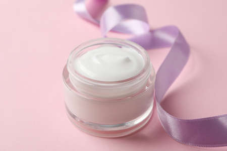 Jar of winter cream for skin on pink background, space for text. Closeup