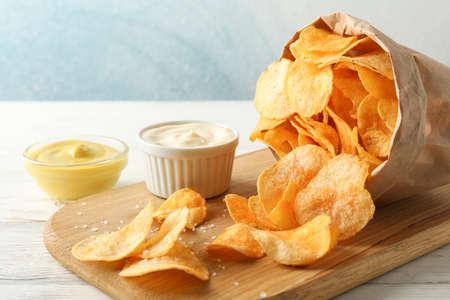 Papiertüte Kartoffelchips. Biersnacks, Sauce auf Schneidebrett, auf weißem Holzhintergrund, Platz für Text. Nahaufnahme