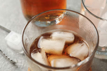 Bottle, glasses with ice cubes and whiskey on grey background, close up