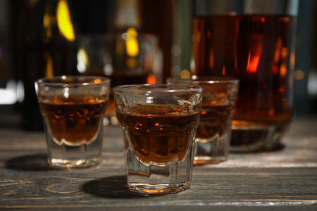 Whiskey shots on wooden table, close up