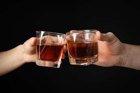 Male hands holds glasses of whiskey on black background, close up. Cheers Stockfoto