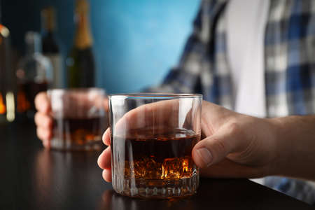 Men holding glasses of whiskey at the bar, space for text