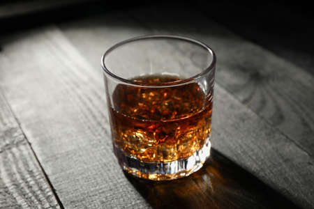 Glass of whiskey with ice cubes on dark wooden background, space for text Reklamní fotografie