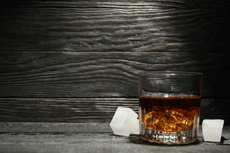 Glass of whiskey and ice cubes on dark wooden background, space for text