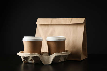 Eco - friendly package and coffee cups on black background, space for text
