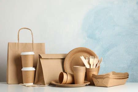 Stoviglie eco-compatibili e sacchetto di carta sul tavolo bianco, spazio per il testo