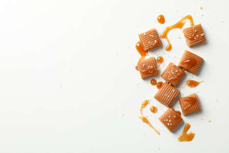 Salted caramel candies and sauce on white background, space for text Фото со стока