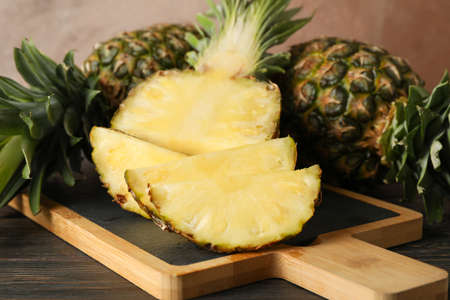 Cutting board with pineapples on wooden background, close up Фото со стока