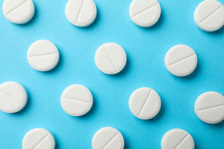 Flat lay with pills on blue background, close up and top view