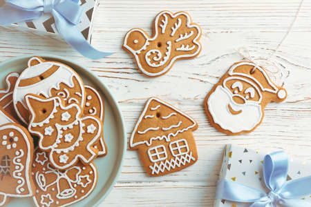 Plate with Christmas cookies, gift box on white wooden background, space for text. Top view