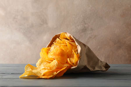 Paper bag of potato chips on gray wooden background, space for text.