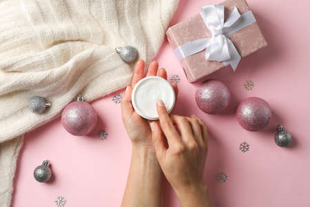 Woman holding jar of cream, warm sweater, gift boxes on pink background, space for text. Top view