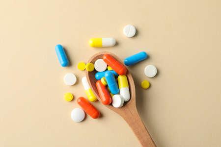 Łyżka i tabletki na beżowym tle, miejsce na tekst