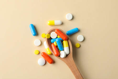 Spoon and pills on beige background, space for text