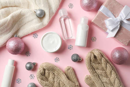 Set cosmetics, winter cream for skin, warm sweater and gloves on pink background, space for text. Top view