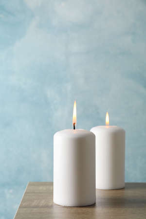 Two burning candles on grey table against blue background, space for text Zdjęcie Seryjne