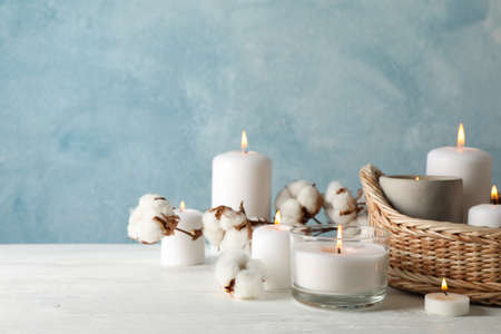 Burning candles, basket and cotton on white wooden table, space for text Archivio Fotografico - 135268506