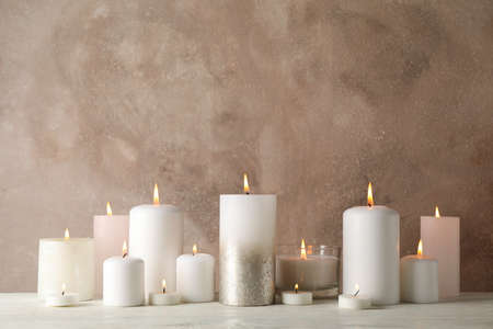 Burning candles on white wooden table against brown background, space for text