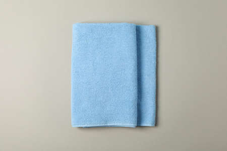Fresh blue towel on grey background, top view Фото со стока
