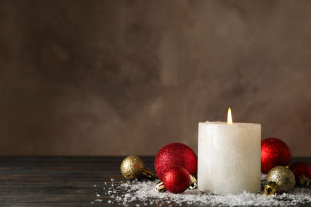 Burning candle and christmas balls on wooden background with snow, space for text