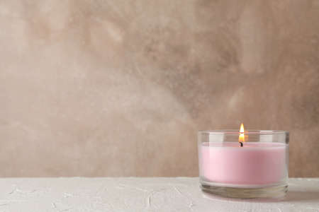 Pink candle in glass jar on white table, space for text